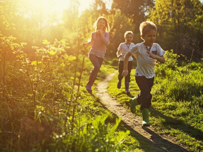 Three children running outside